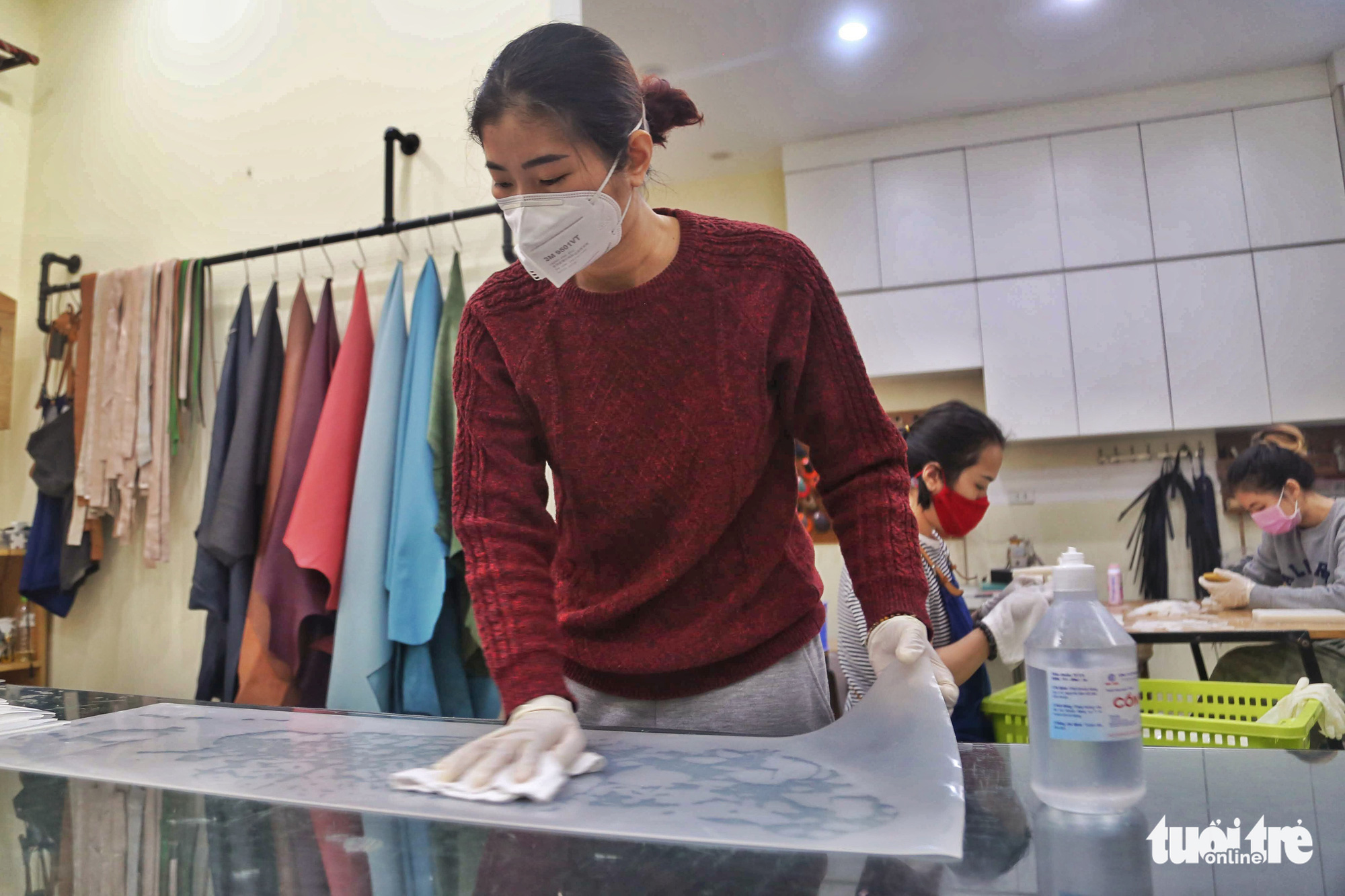 A worker disinfects a silicon sheet with alcohol at an ear guard making facility in Hanoi, Vietnam. Photo: Mai Thuong / Tuoi Tre