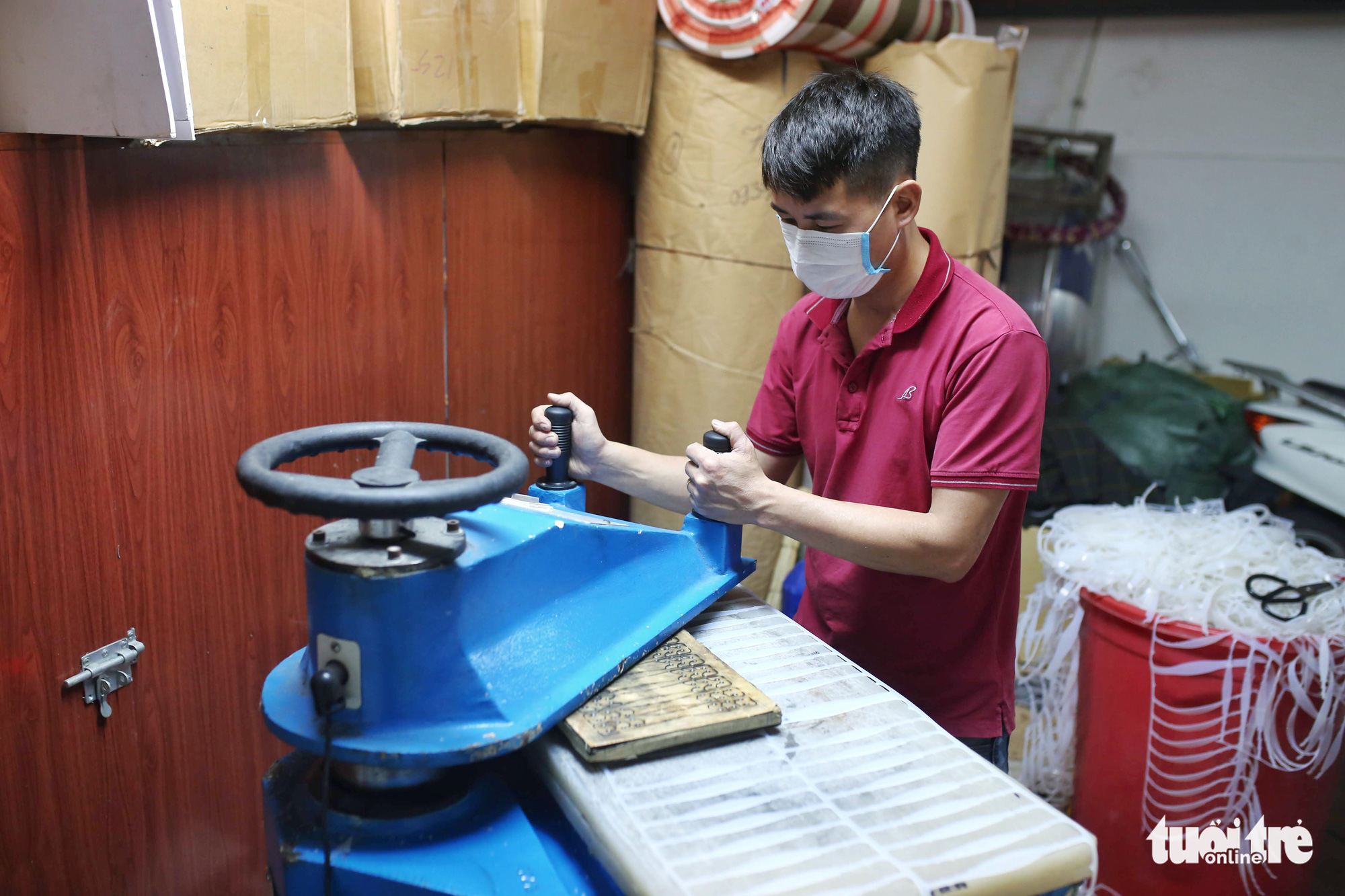 A worker operates a hydraulic press to stamp out ear guards from a silicon sheet at a facility in Hanoi, Vietnam. Photo: Mai Thuong / Tuoi Tre