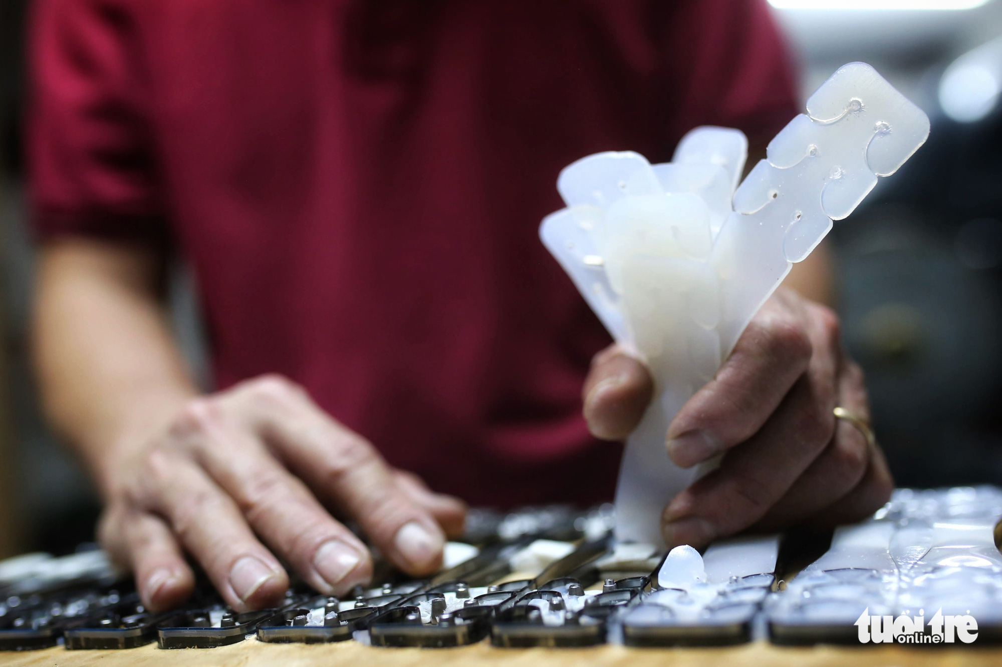 A worker removes ear guards from the mould at a facility in Hanoi, Vietnam. Photo: Mai Thuong / Tuoi Tre
