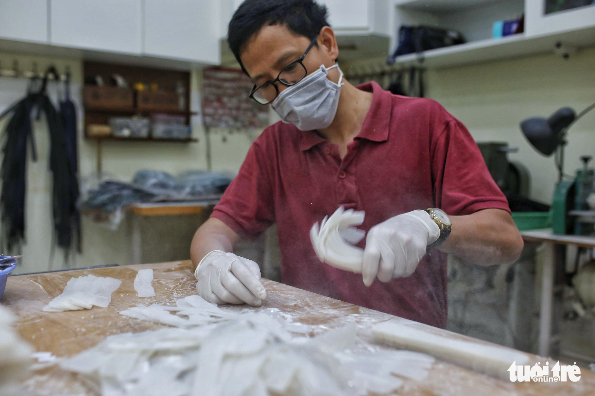 Phan Manh Ha, a member of the volunteer Anti COVID-19 group, shakes excess talc powder off finished ear guards before packaging at a facility in Hanoi, Vietnam. Photo: Mai Thuong / Tuoi Tre