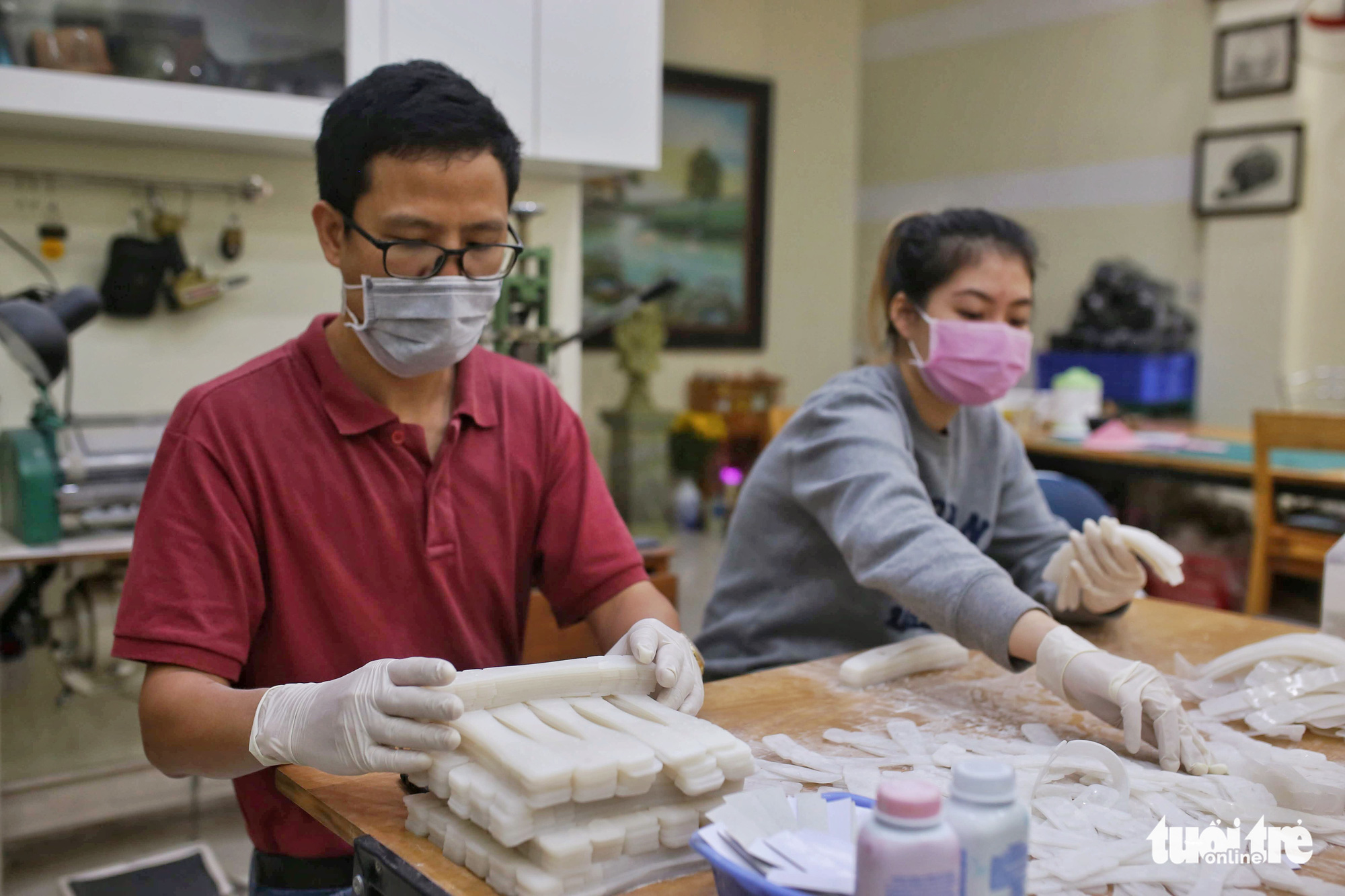 Workers package finished ear guards for delivery to hospitals at a facility in Hanoi, Vietnam. Photo: Mai Thuong / Tuoi Tre