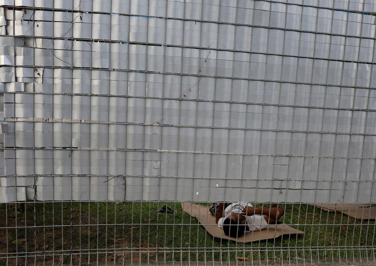FILE PHOTO: A migrant worker rests on the ground behind the fence of the Punggol S11 dormitory during the coronavirus outbreak (COVID-19) in Singapore April 6, 2020.  Photo: Reuters