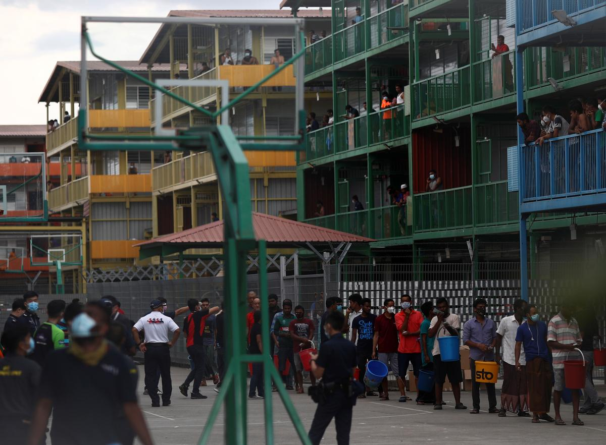 FILE PHOTO: Migrant workers queue to collect food at the Punggol S11 dormitory during the coronavirus outbreak (COVID-19) in Singapore April 6, 2020.  Photo: Reuters