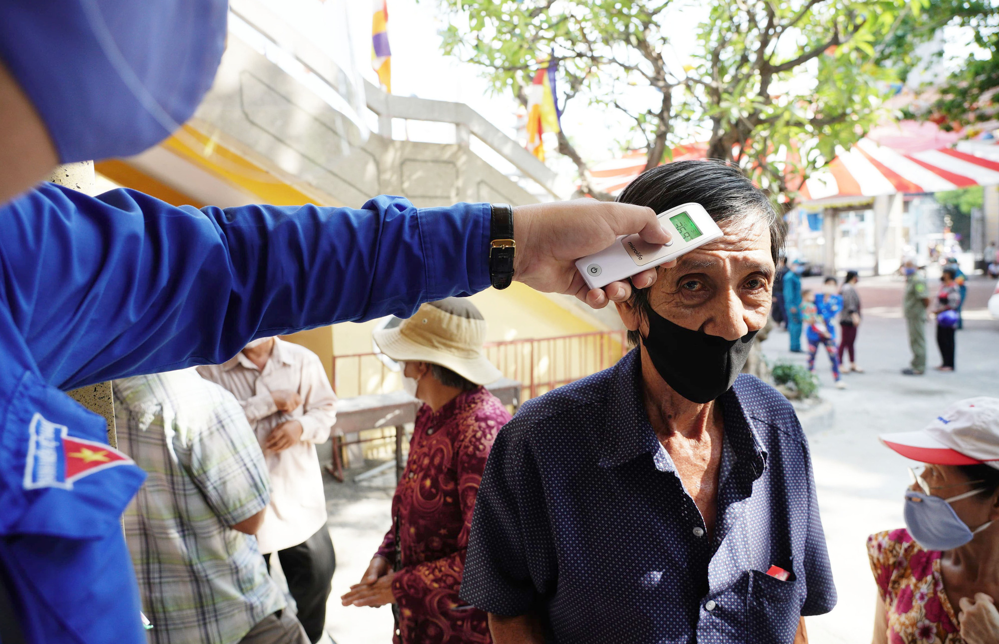 A volunteer checks the body temperature of a customer at the entrance of the 'Zero-VND Happy Supermarket' located at Vinh Nghiem Pagoda in District 3, Ho Chi Minh City, Vietnam. Photo: Duyen Phan / Tuoi Tre