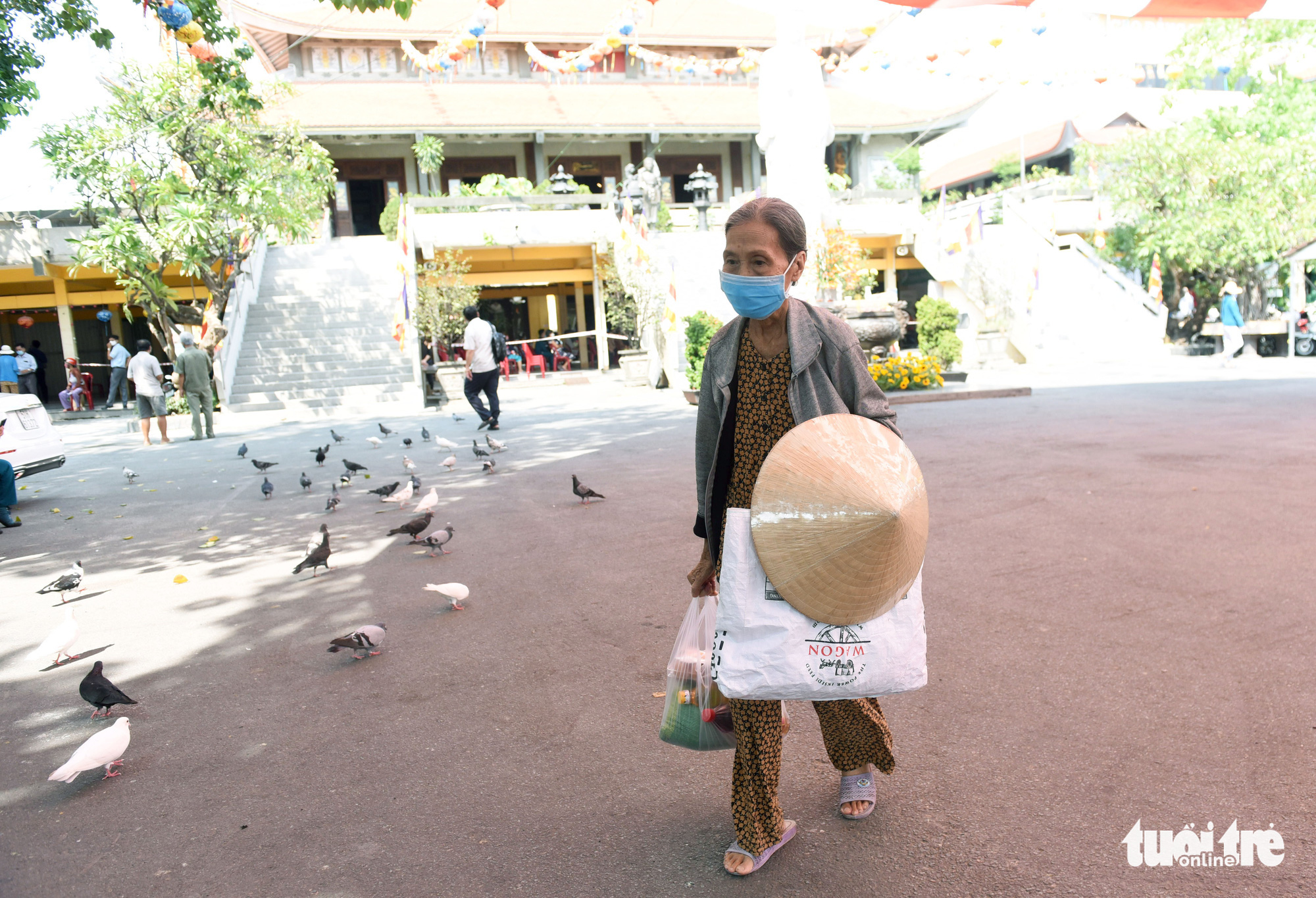 An elderly customer leaves after having obtained the staples she needs from the 'Zero-VND Happy Supermarket' located at Vinh Nghiem Pagoda in District 3, Ho Chi Minh City, Vietnam. Photo: Duyen Phan / Tuoi Tre