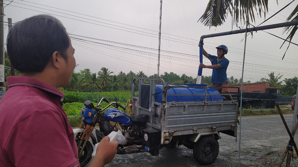 A local resident in Cho Lach District, Ben Tre Province in Vietnam's Mekong Delta pumps fresh water from Le Van Chen (left)'s reservoir into a container on a vehicle. Photo: Tien Trinh / Tuoi Tre