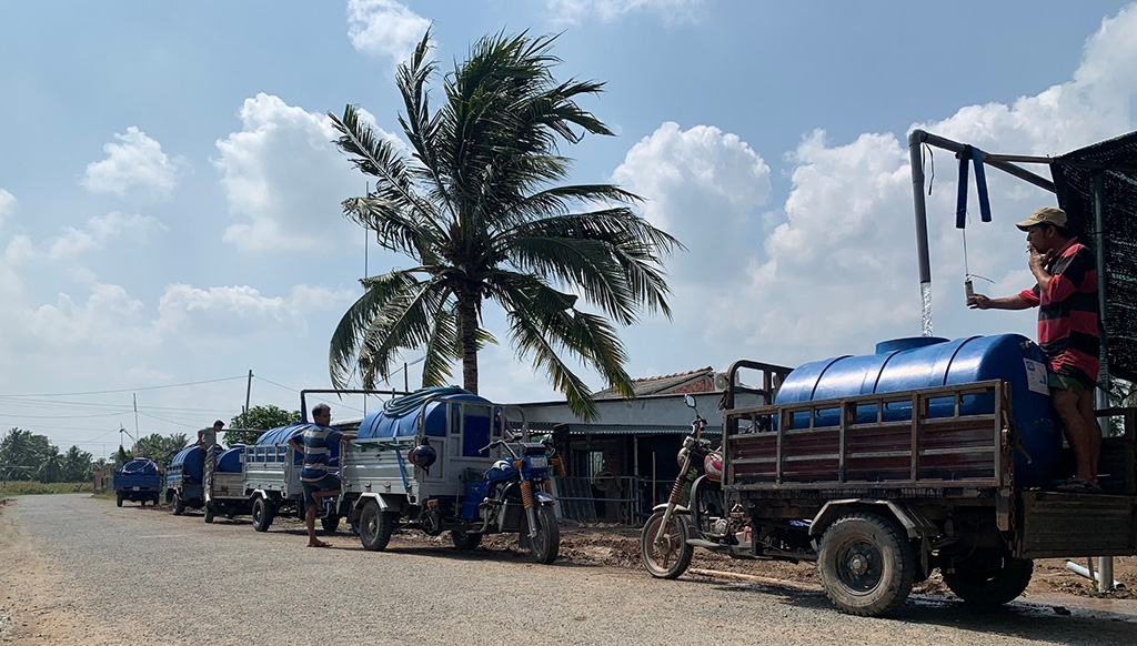 Vehicles line up to collect fresh water from Le Van Chen's reservoir in Cho Lach District, Ben Tre Province in Vietnam's Mekong Delta. Photo: Tien Trinh / Tuoi Tre