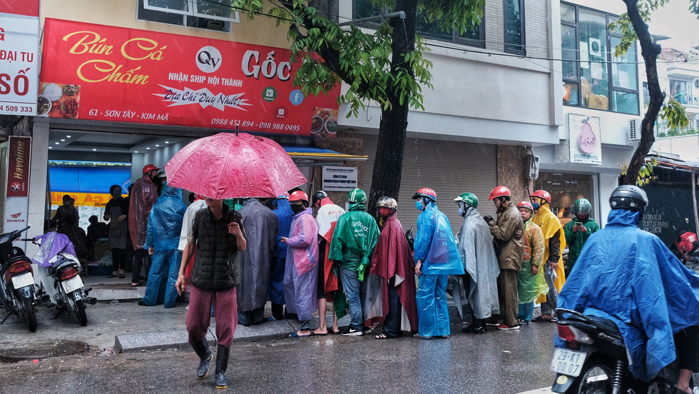 Food delivery workers queue in front of a restaurant in Hanoi, Vietnam after COVID-19 social distancing measures were relaxed in the capital city. Photo: Mai Thuong / Tuoi Tre