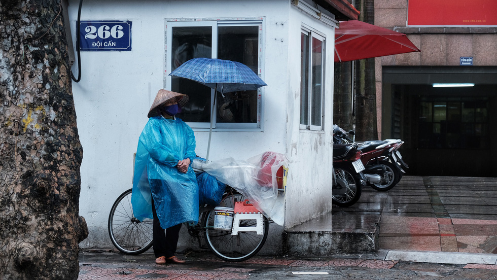 A street vendor takes shelter from the rain as she's back on the street to make a living after COVID-19 social distancing measures were relaxed in Hanoi, Vietnam. Photo: Mai Thuong / Tuoi Tre