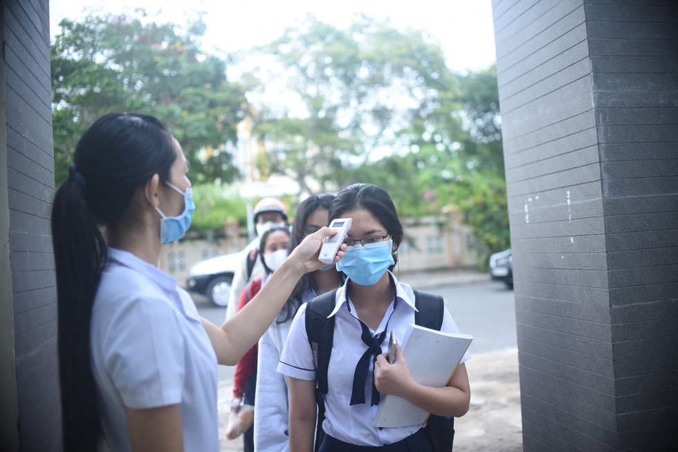 A student checks the body temperature of another on their first day back at school after a three-month COVID-19 break at Luong Van Chanh High School in Phu Yen Province, Vietnam, April 27, 2020. Photo: Lam Thien / Tuoi Tre