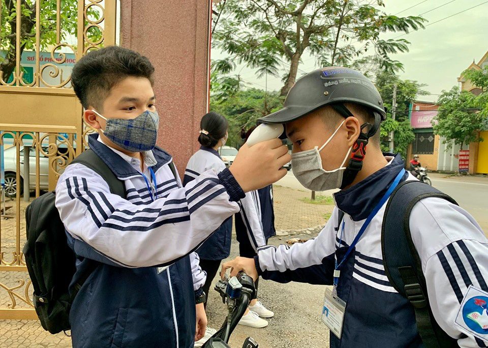 A student checks the body temperature of another on their first day back at school after a three-month COVID-19 break at Le Viet Thuat High School in Vinh City, Nghe An Province, Vietnam, April 27, 2020. Photo: Doan Hoa / Tuoi Tre