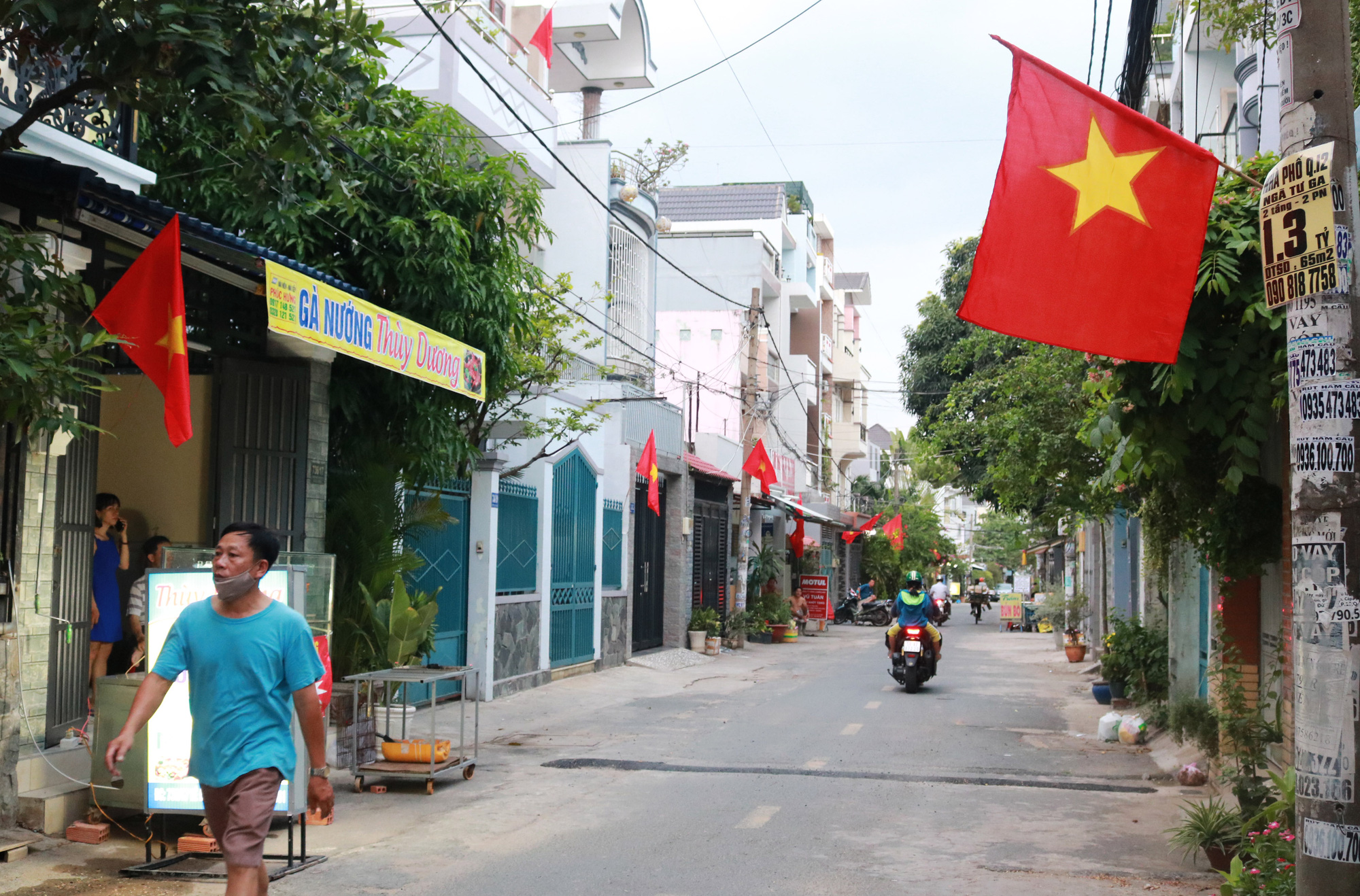 Residents hang national flags in front of their homes along a street in Go Vap District, Ho Chi Minh City to celebrate Vietnam's National Day on April 30, 2020. Photo: Nhat Thinh / Tuoi Tre