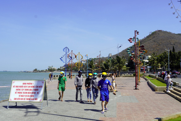 People walk past a signboard propagandizing COVID-19 prevention measures and banning beach at a park near the beach in Vung Tau Province, Vietnam, April 30, 2020. Photo: Dong Ha / Tuoi Tre