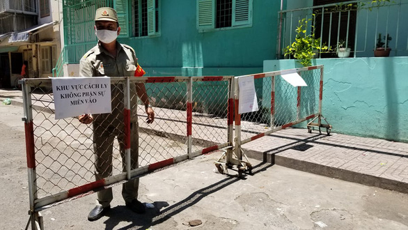 A man guards at the entrance to a sealed-off apartment building on Nguyen Dinh Chieu Street in District 1, Ho Chi Minh City, May 1, 2020 after COVID-19 patient No.92, who lives there, had a relapse. Photo: Chau Tuan / Tuoi Tre