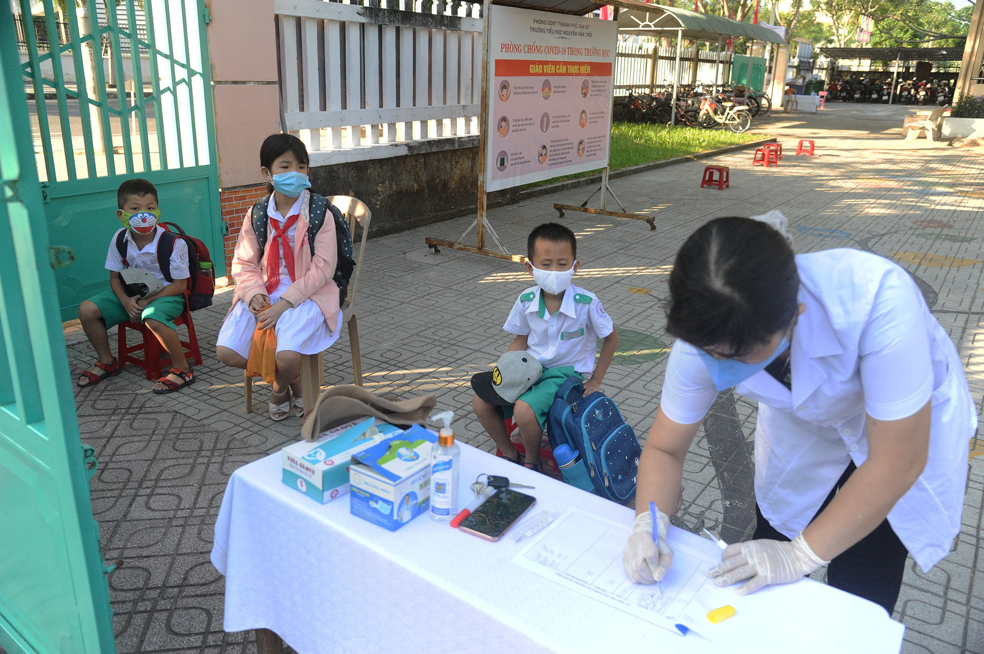 Elementary school students in Quang Nam Province have their health monitored before entering the school on May 4, 2020. Photo: Le Trung / Tuoi Tre