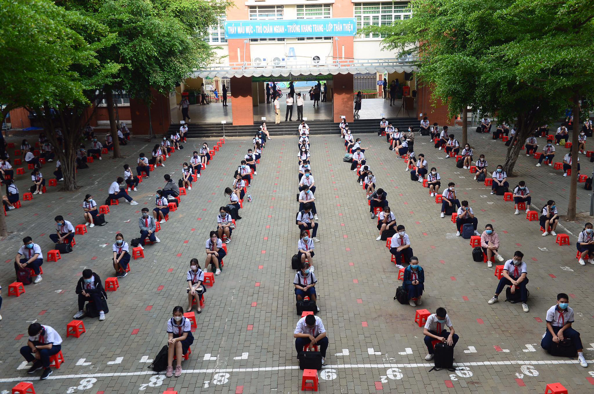 Students of Le Van Tam Middle School in Ho Chi Minh City keep distance from each other inside the school yard on May 4, 2020. Photo: Quang Dinh / Tuoi Tre