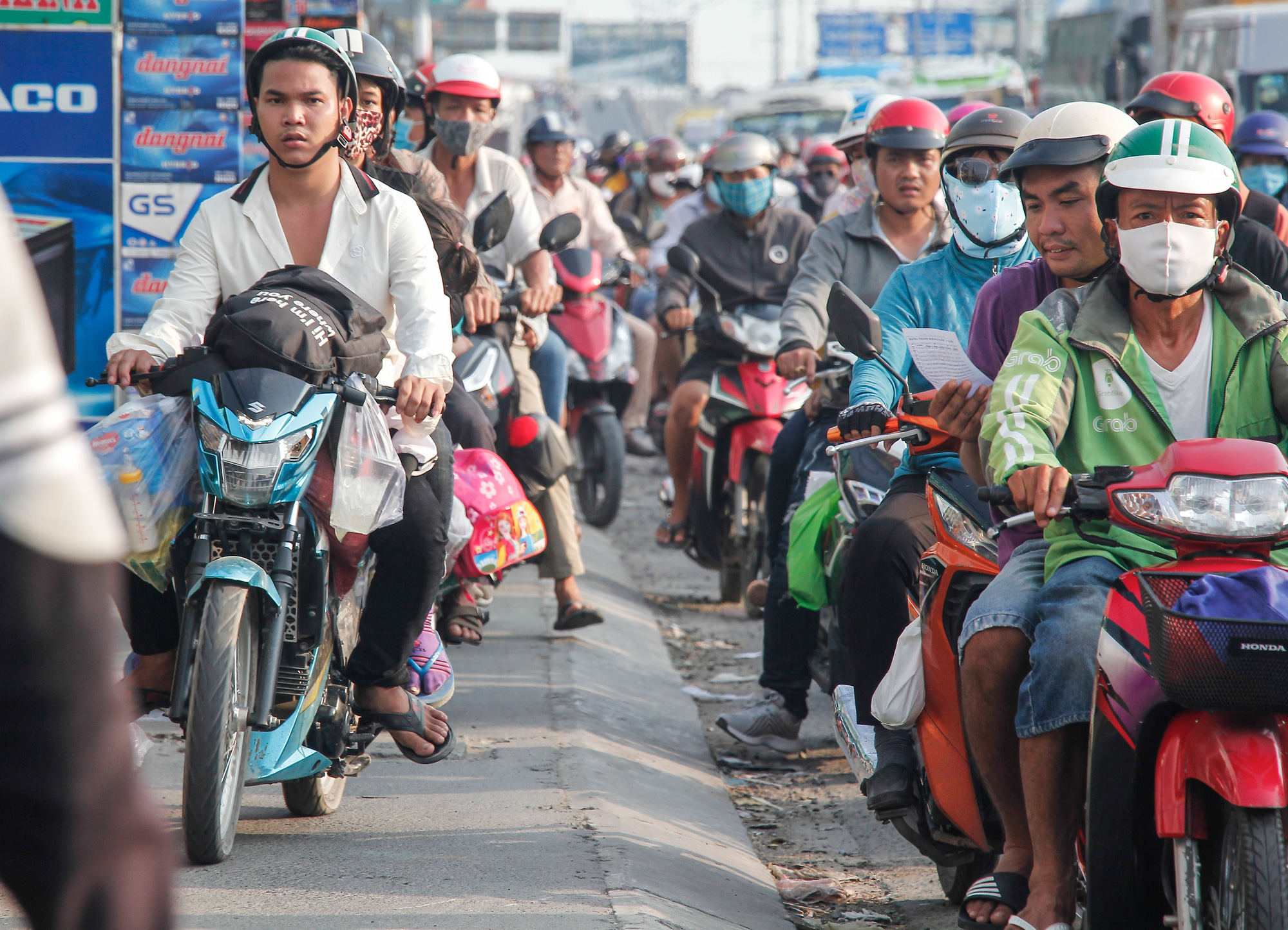 Motorcyclists travel on the sidewalk amid a traffic jam on National Highway 1 leading to Ho Chi Minh City, May 3, 2020. Photo: Chau Tuan / Tuoi Tre