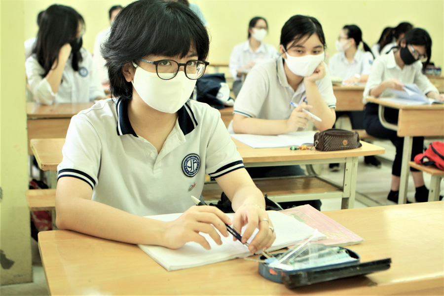 Students wear face masks and plastic shields inside a classroom of Yen Hoa High School in Hanoi on May 4, 2020. Photo: Vinh Ha / Tuoi Tre