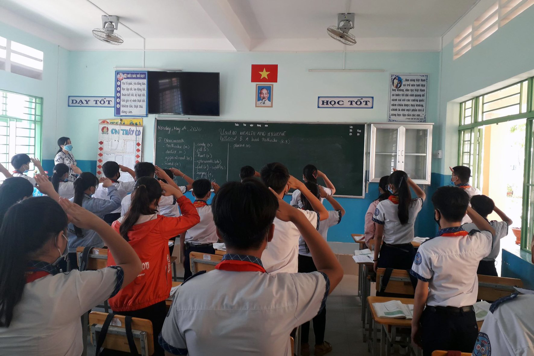 Students at a middle school in Dong Nai Province attend the flag-raising ceremony inside the classroom instead of the school yard on May 4, 2020. Photo: H.S. / Tuoi Tre