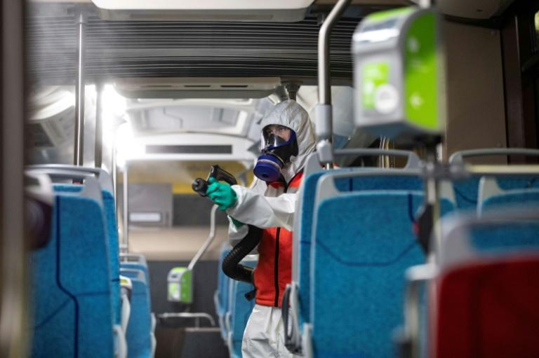 An employee of a cleaning company disinfects a bus on the outskirts of Paris. Photo: AFP