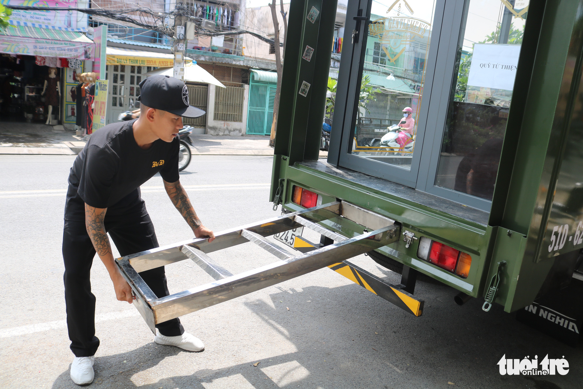 An employee lowers a collapsible ladder from a mobile barbershop offering free haircuts in Ho Chi Minh City, Vietnam. Photo: Ngoc Phuong / Tuoi Tre