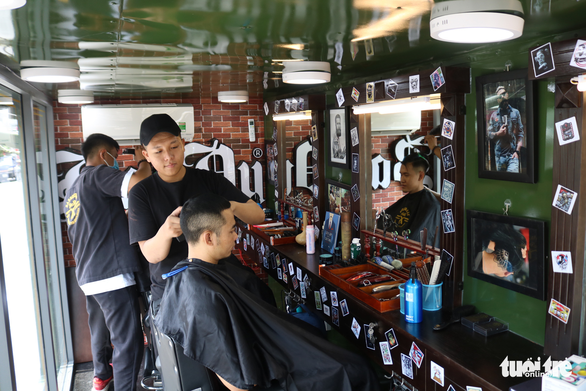 Barbers give free haircuts to customers inside a mobile barbershop in Ho Chi Minh City, Vietnam. Photo: Ngoc Phuong / Tuoi Tre