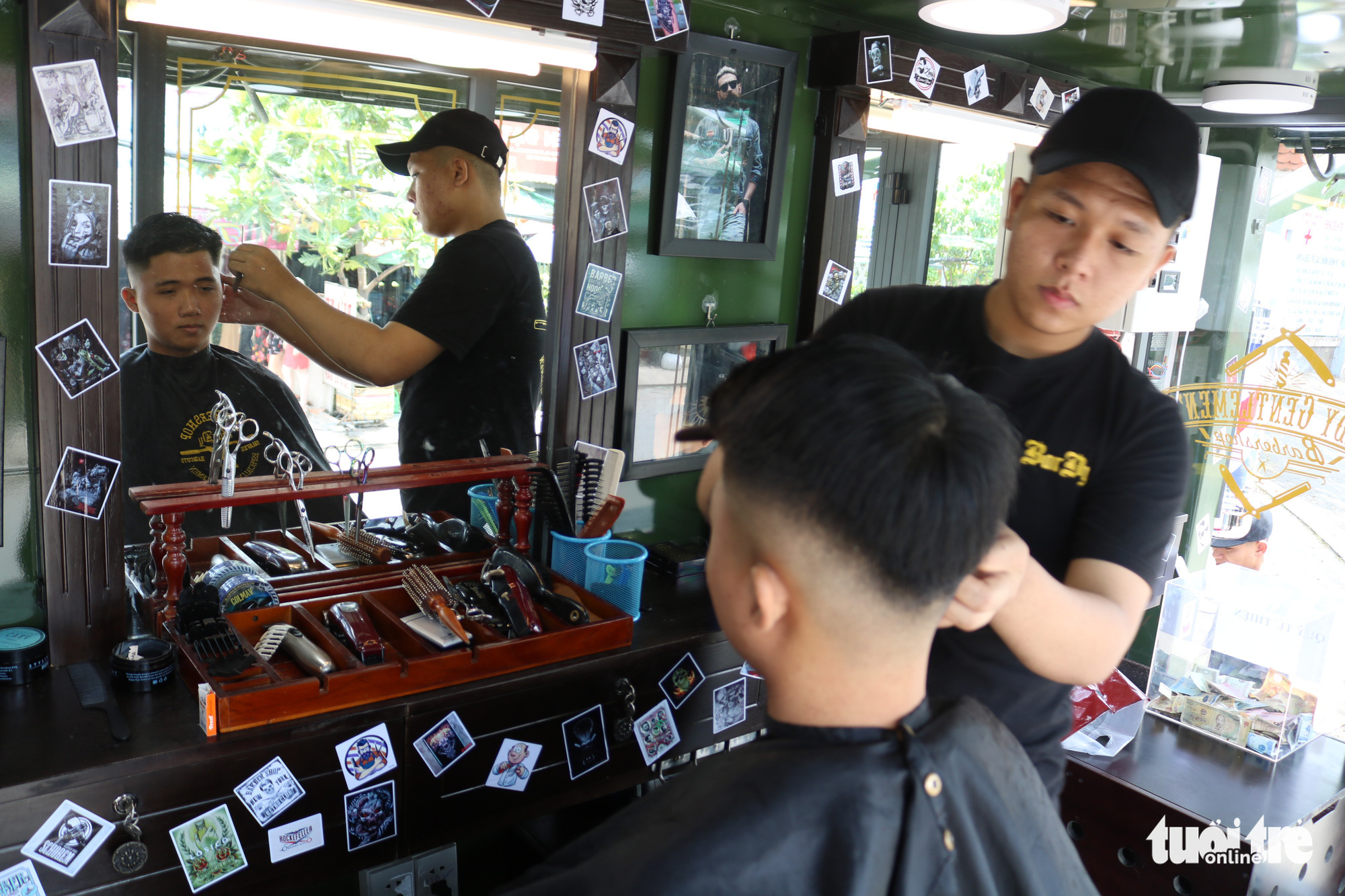 A barber gives a free haircut to a customer inside a mobile barbershop in Ho Chi Minh City, Vietnam. Photo: Ngoc Phuong / Tuoi Tre