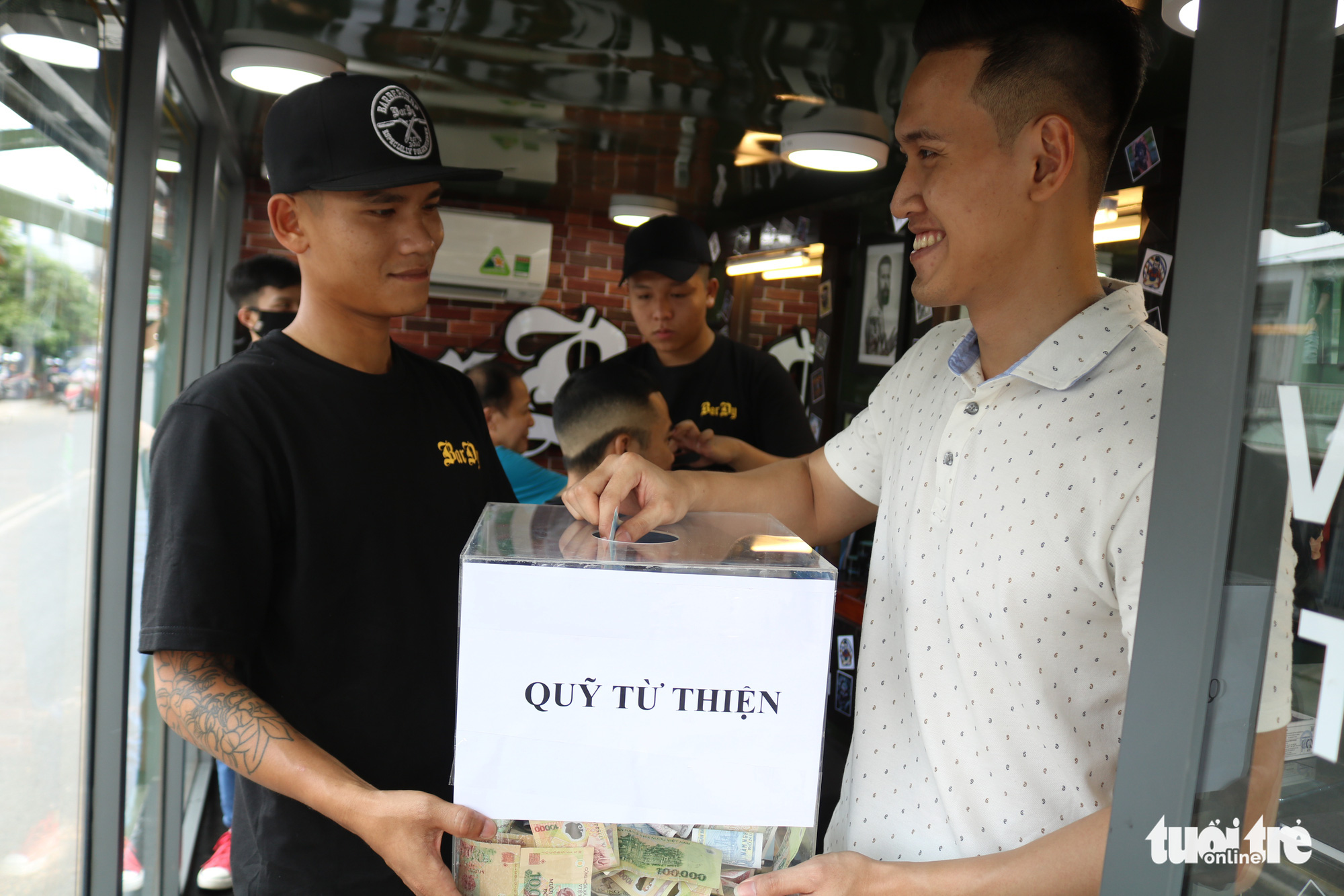 Nguyen Minh Phuc (right), a 24-year-old resident in District 12, Ho Chi Minh City, makes a donation after getting a free haircut at a Vietnamese mobile barbershop backed by charitable purposes. Photo: Ngoc Phuong / Tuoi Tre