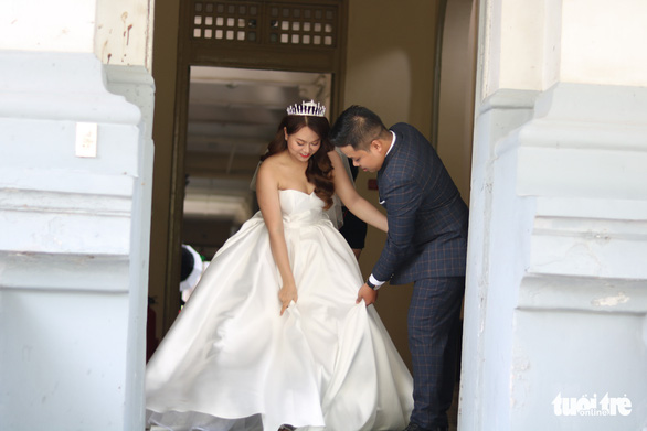 Trinh Hoang Dong helps his bride-to-be walk in her gown while the two are taking pre-wedding photos in Ho Chi Minh City, Vietnam, May 13, 2020. Photo: Ngoc Phuong / Tuoi Tre