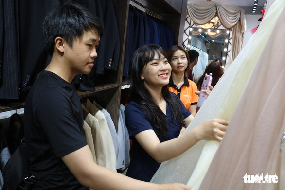 Tuan (left), 26, and My Thuy, 25, are seen picking wedding gowns at a bridal store on Ho Van Hue Street in Phu Nhuan District, Ho Chi Minh City, Vietnam, May 13, 2020. Photo: Ngoc Phuong / Tuoi Tre
