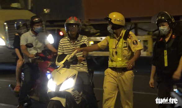 Traffic police pulls over a motorbike driver for administrative inspecting in Ho Chi Minh City on May 15, 2020. Photo: Minh Hoa/ Tuoi Tre