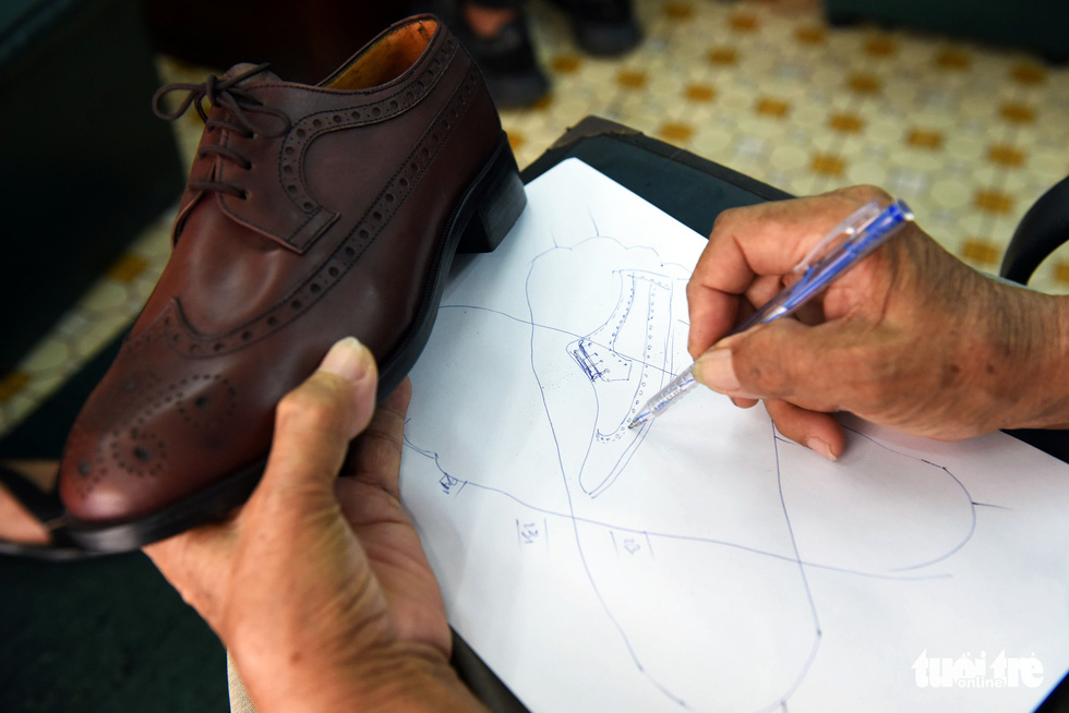 Ngoc sketches shoes on paper before making them by hand. Photo: Duyen Phan / Tuoi Tre