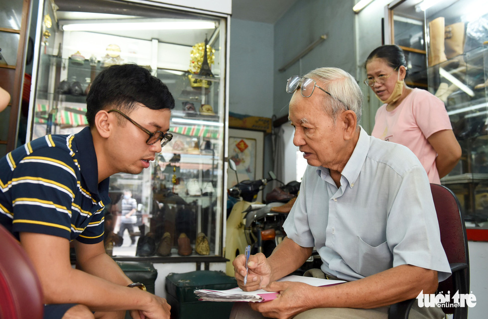 Nham (left), 28, flew from Hanoi to meet Ngoc and order a pair of shoes from the artisan. Photo: Duyen Phan / Tuoi Tre