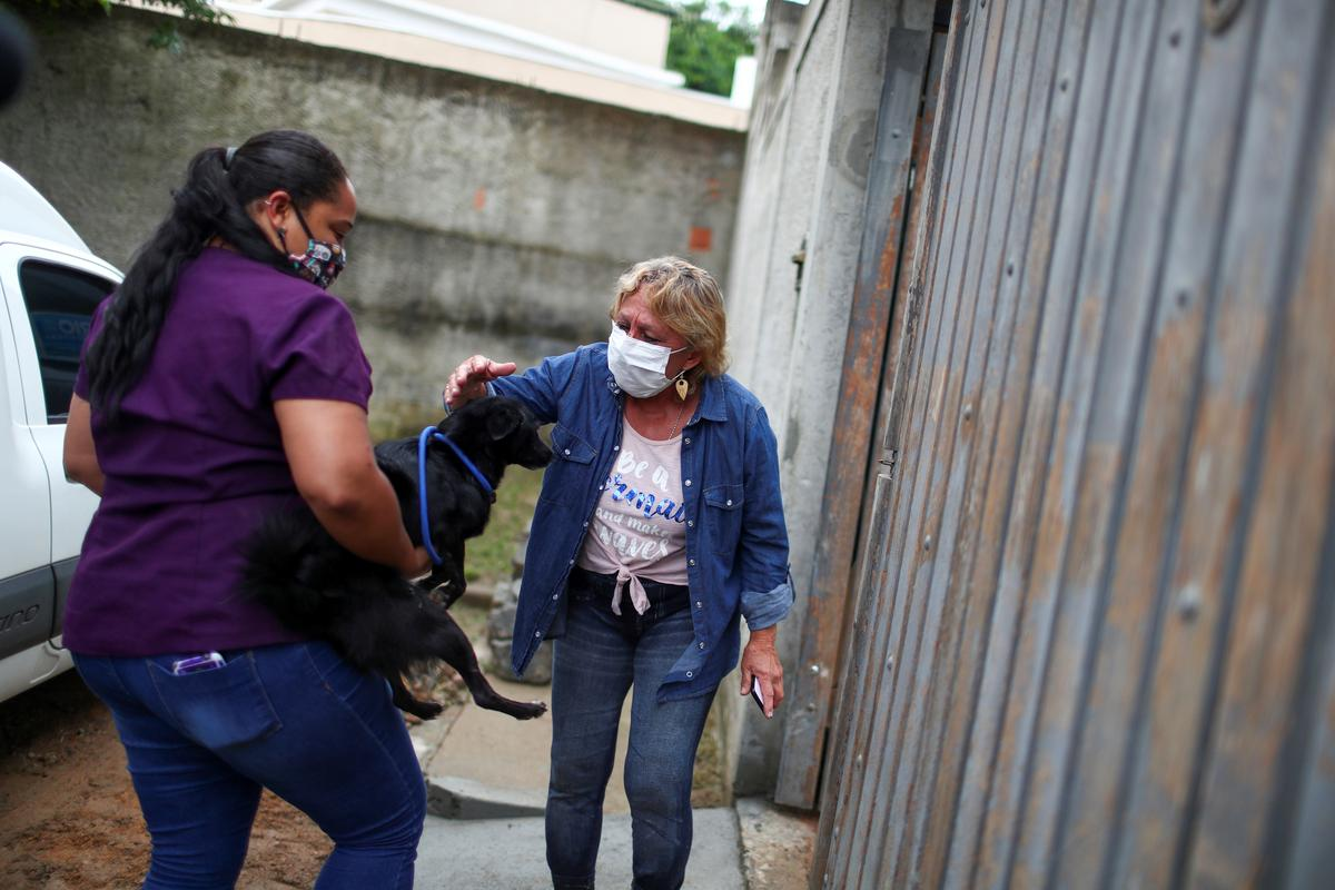Maria de Fatima Cordeiro Marques, who recovered from the coronavirus disease, pets her adopted dog Sansa as she arrives at home, as a part of a pet delivery campaign to find homes for abandoned animals managed by Rio de Janeiro City Hall during the coronavirus disease (COVID-19) outbreak, in Rio de Janeiro, Brazil May 15, 2020. Photo: Reuters
