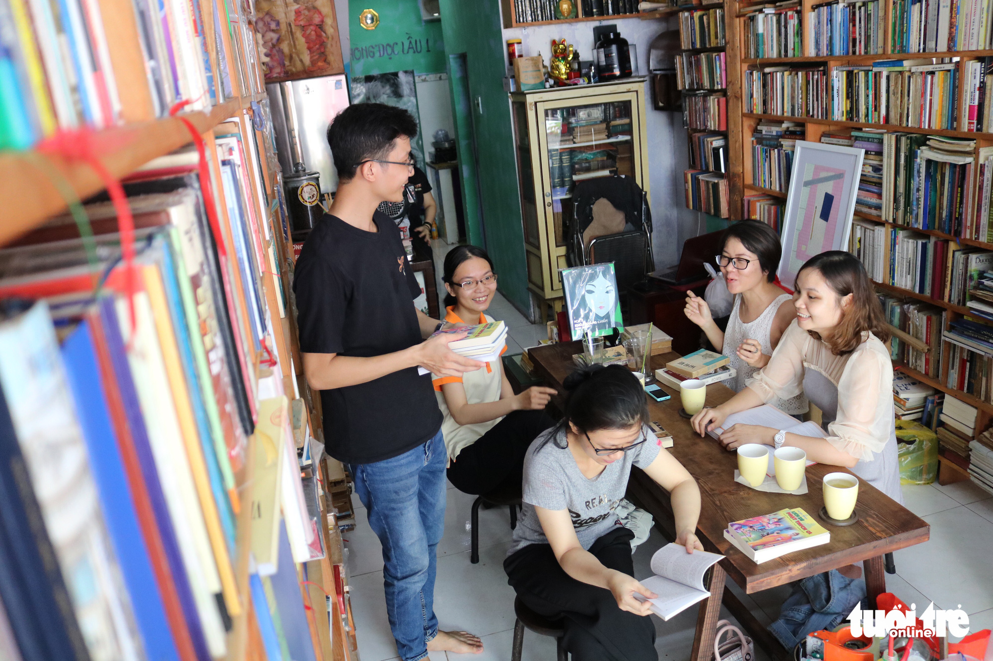 Le Ba Tan (left), owner of the bookstore-café on Nguyen Khac Nhu Street in Ho Chi Minh City, Vietnam, talks to visitors. Photo: Ngoc Phuong / Tuoi Tre