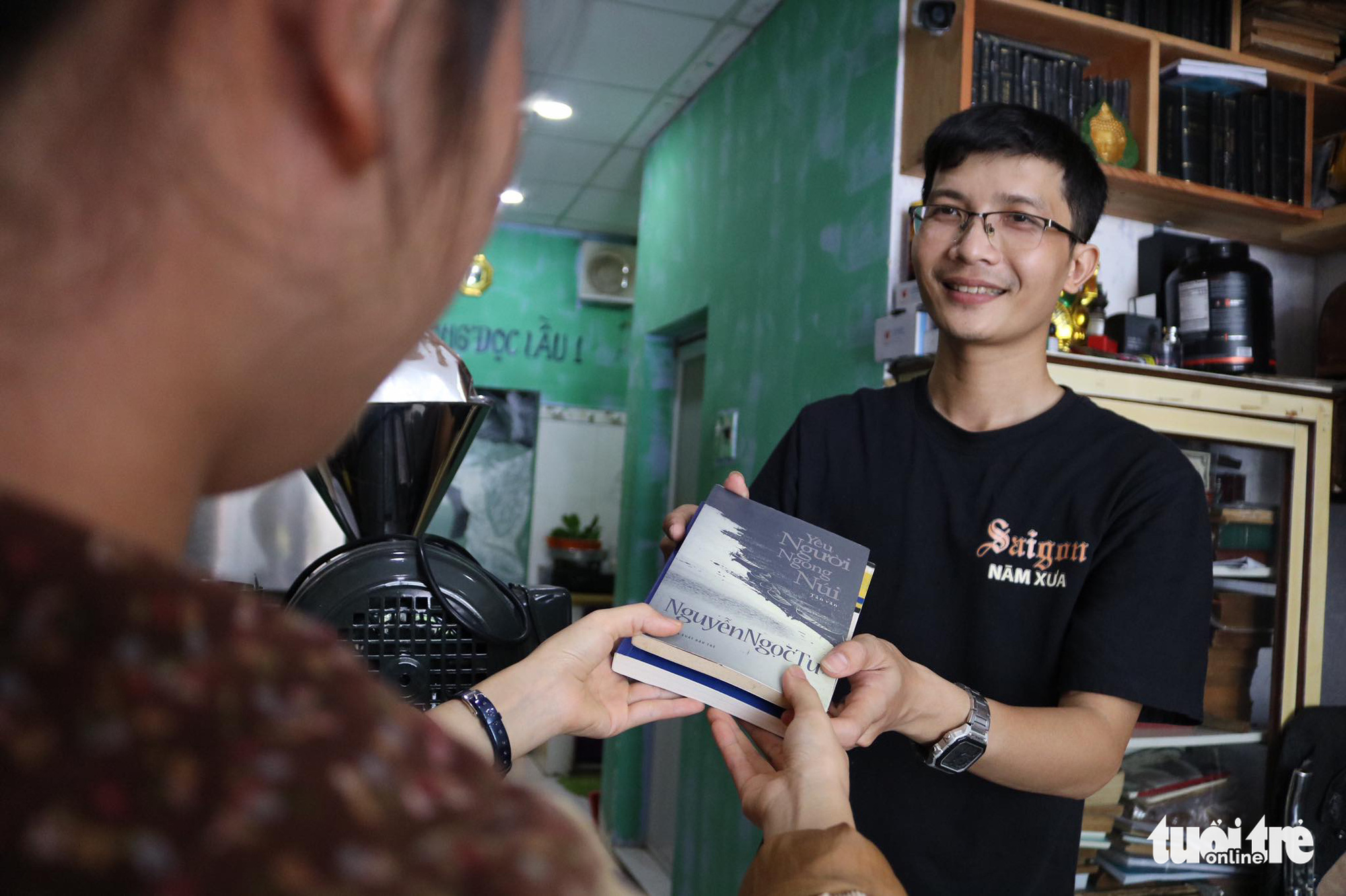 Le Ba Tan (right) accepts books from a visitor in return for a beverage he offered at a bookstore-café on Nguyen Khac Nhu Street in Ho Chi Minh City, Vietnam. Photo: Ngoc Phuong / Tuoi Tre