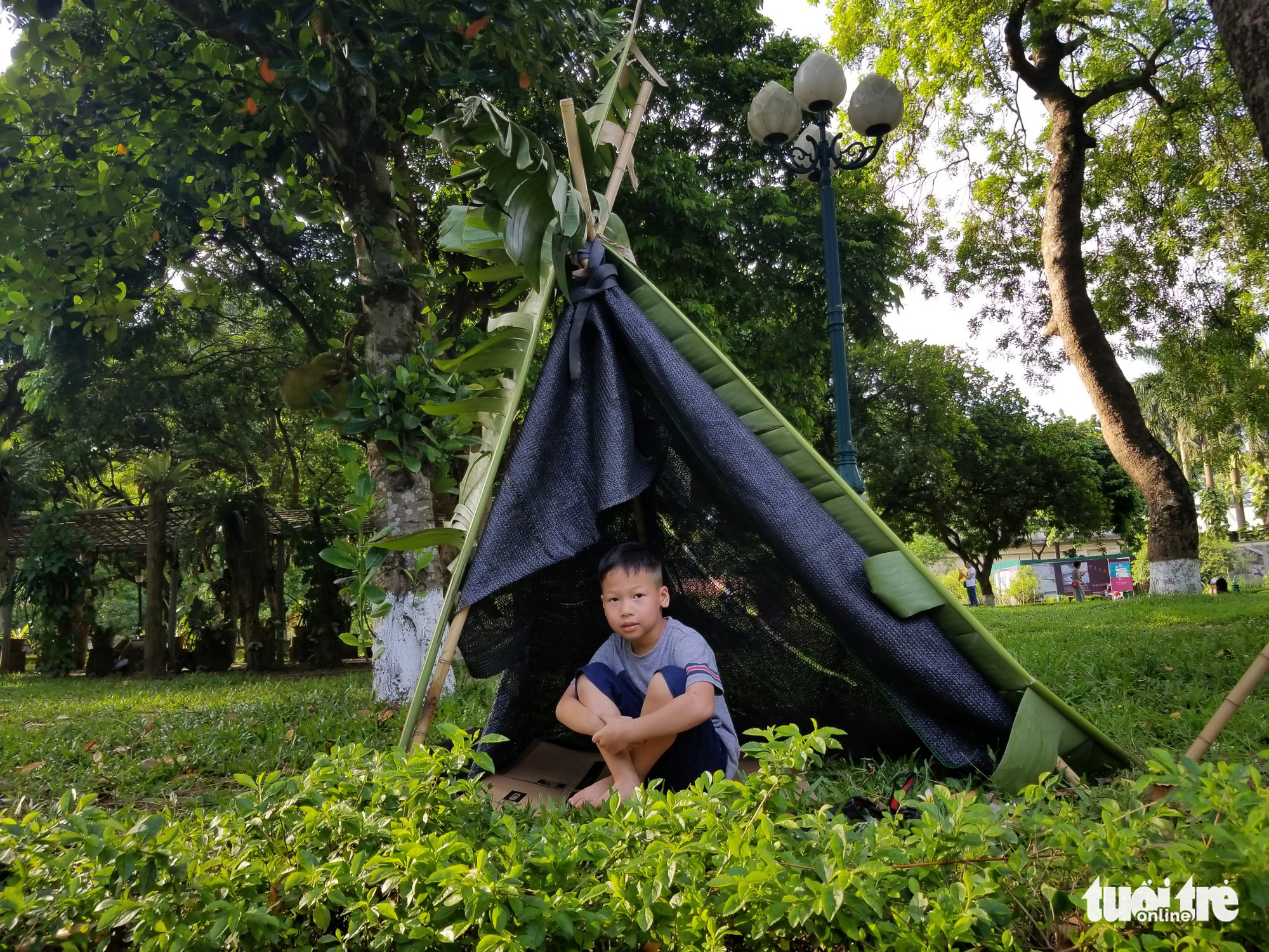 A boy sits in a tent made from canvases banana leaves at the 'Kingdom of Recycled Materials' event in Hanoi, Vietnam, May 31, 2020. Photo: Ha Thanh / Tuoi Tre