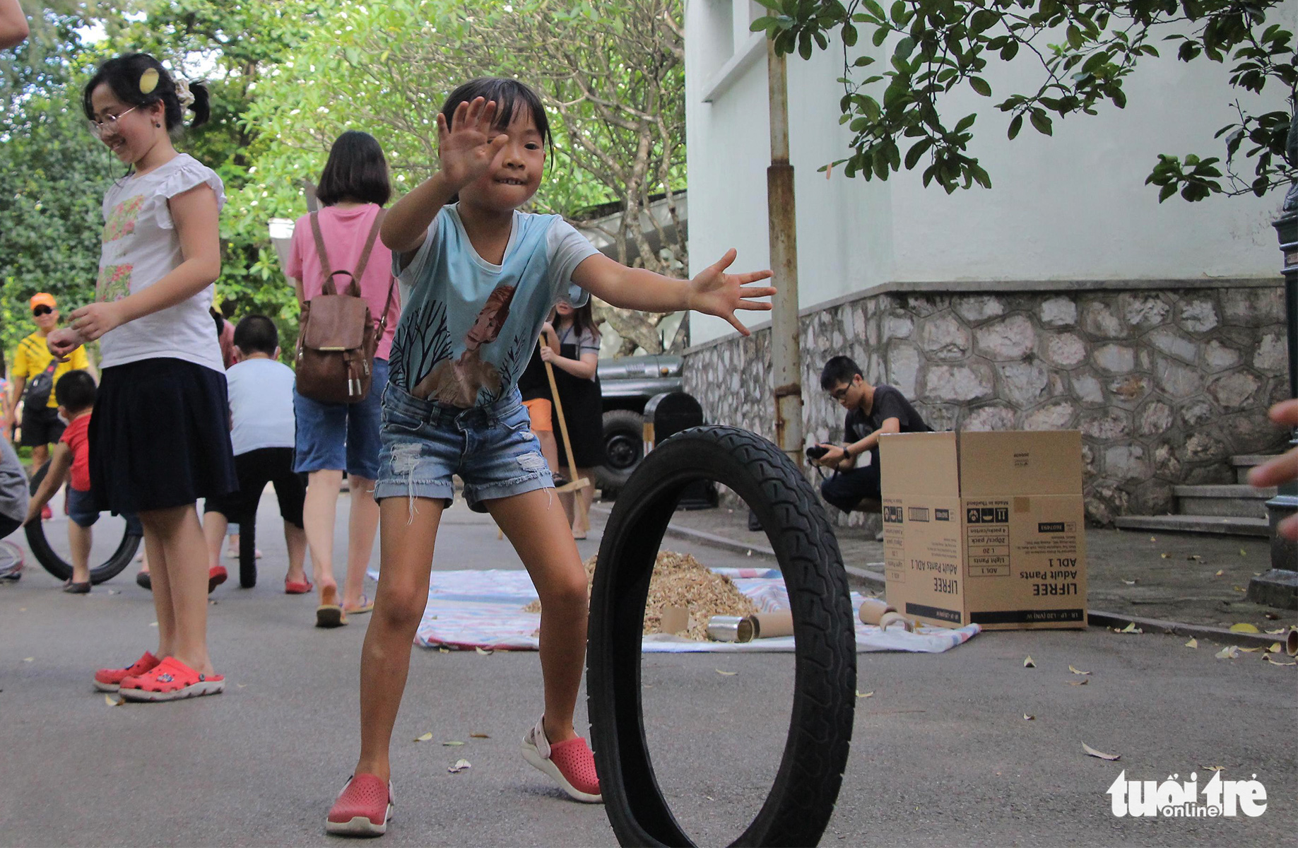 A girl plays with an old tire at the 'Kingdom of Recycled Materials' event in Hanoi, Vietnam, May 31, 2020. Photo: Ha Thanh / Tuoi Tre