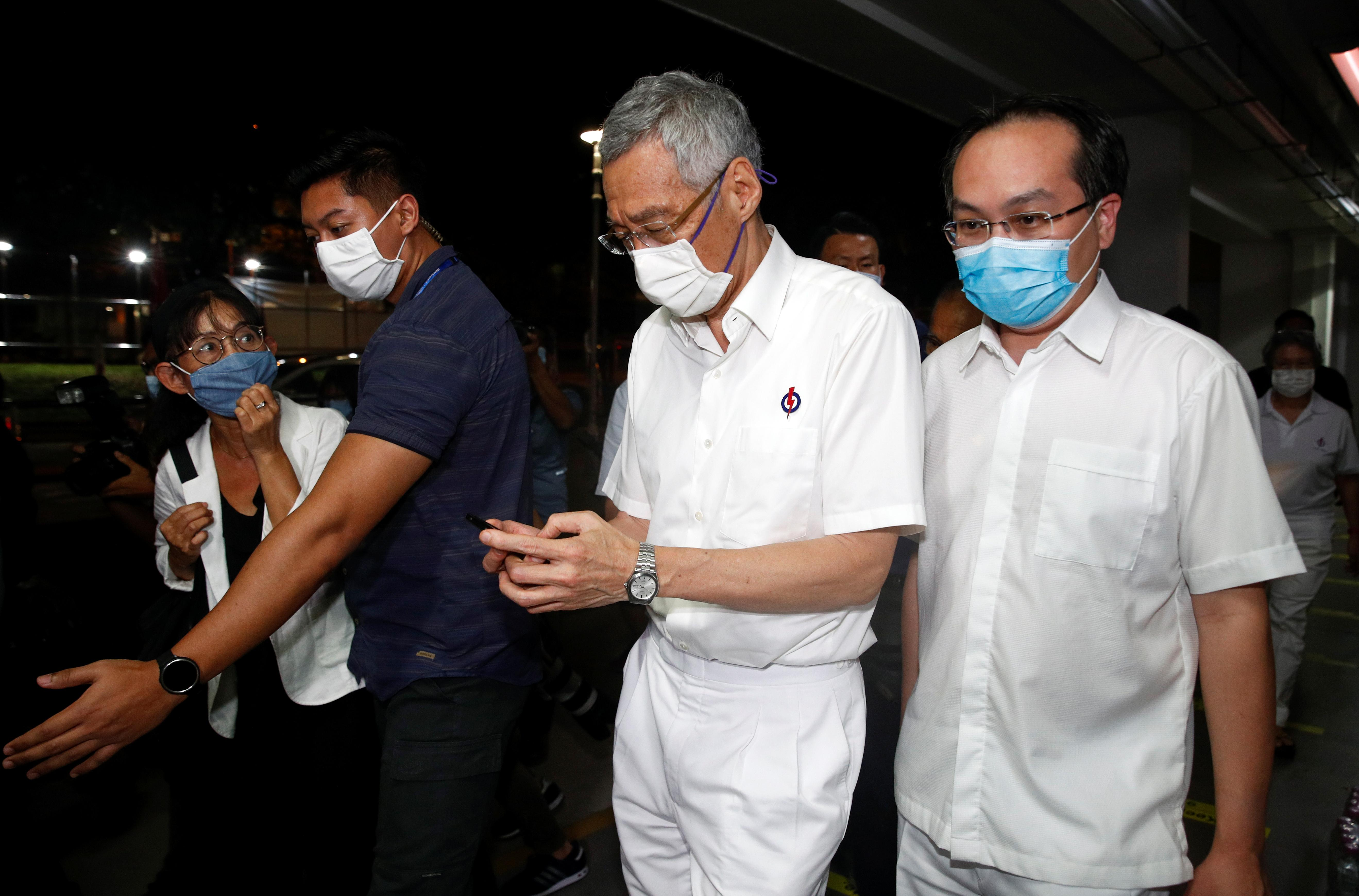 Singapore's Prime Minister Lee Hsien Loong uses a mobile phone at a People's Action Party branch office, as ballots are being counted during the general election, in Singapore July 11, 2020. Photo: Reuters