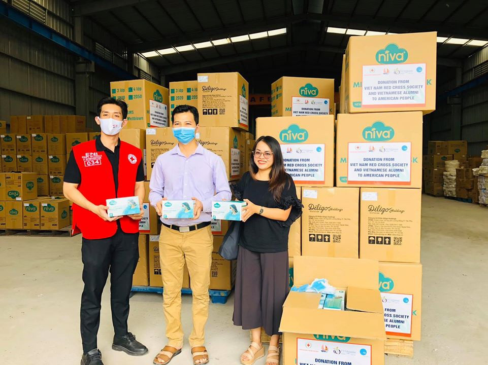 A VUSAC representative (right), a representative from a face masks manufacturer (center) and a staff member of the Vietnam Red Cross Society pose with cargoes of donated face masks before sending them en route to the U.S. in this photo taken in late April 2020.