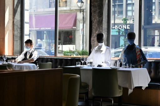 A server (L) wearing a facemask adjusts glasses on a table near mannequins placed to provide social distancing at a Montreal restaurant on July 10, 2020 amid the pandemic; the mannequins' clothes are sold, with profits going to charity. Photo: AFP