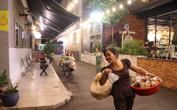Nguyen Thi Loan, a subtenant at a cheap shared home, is seen hawking snacks at night in Tan Phu District, Ho Chi Minh City, Vietnam. Photo: Le Van / Tuoi Tre