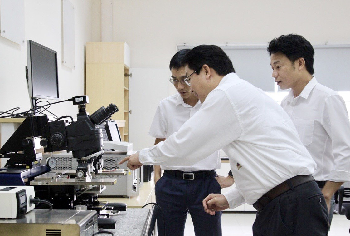 A member of the research team at the University of Technology under Vietnam National University, Ho Chi Minh City shows a piece of research equipment to Viettel representatives. Photo: Dieu Linh / Tuoi Tre