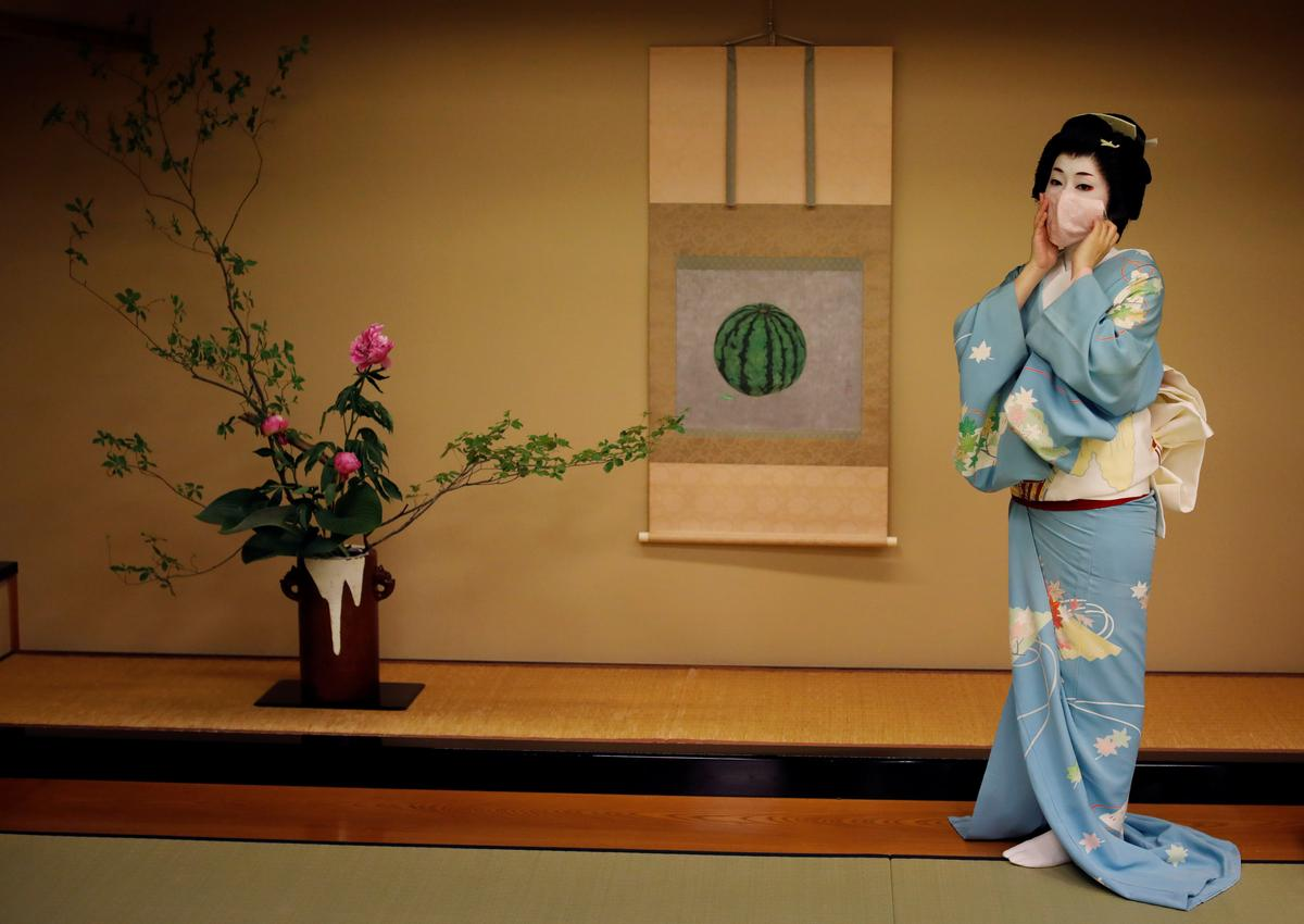 Koiku, who is a geisha, wears a protective face mask to pose for a photograph, before working at a party being hosted by customers, where she will entertain with other geisha, at Asada, a luxury Japanese restaurant, during the coronavirus disease (COVID-19) outbreak, in Tokyo, Japan, June 23, 2020. Photo: Reuters