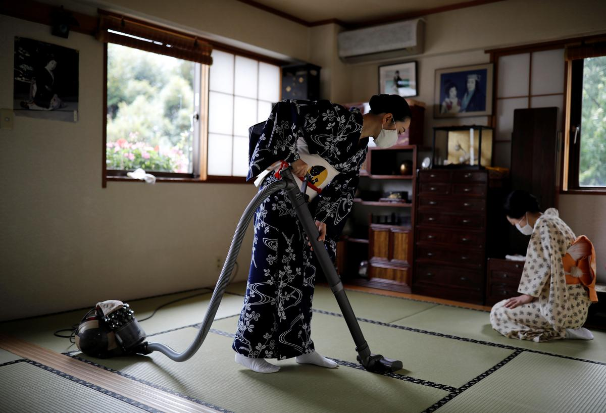 Koiku and Maki, who are geisha, clean Ikuko's living room before they have lunch together at Ikuko's home, during the coronavirus disease (COVID-19) outbreak in Tokyo, Japan, July 11, 2020. Photo: Reuters