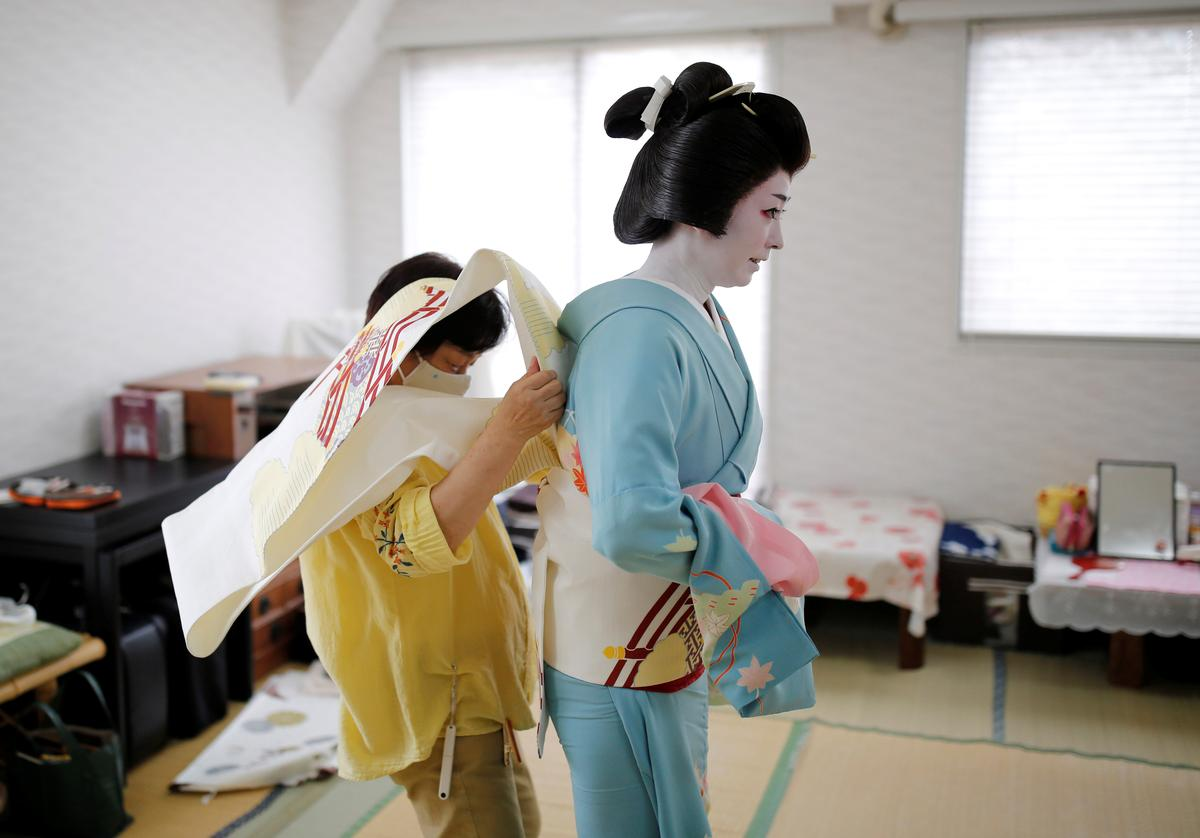 A kimono dresser helps Koiku, who is a geisha, put on her kimono as Koiku gets ready at Ikuko's home to work at a party being hosted by customers at a restaurant, where she will be entertaining with other geisha, during the coronavirus disease (COVID-19) outbreak, in Tokyo, Japan, June 23, 2020. Photo: Reuters