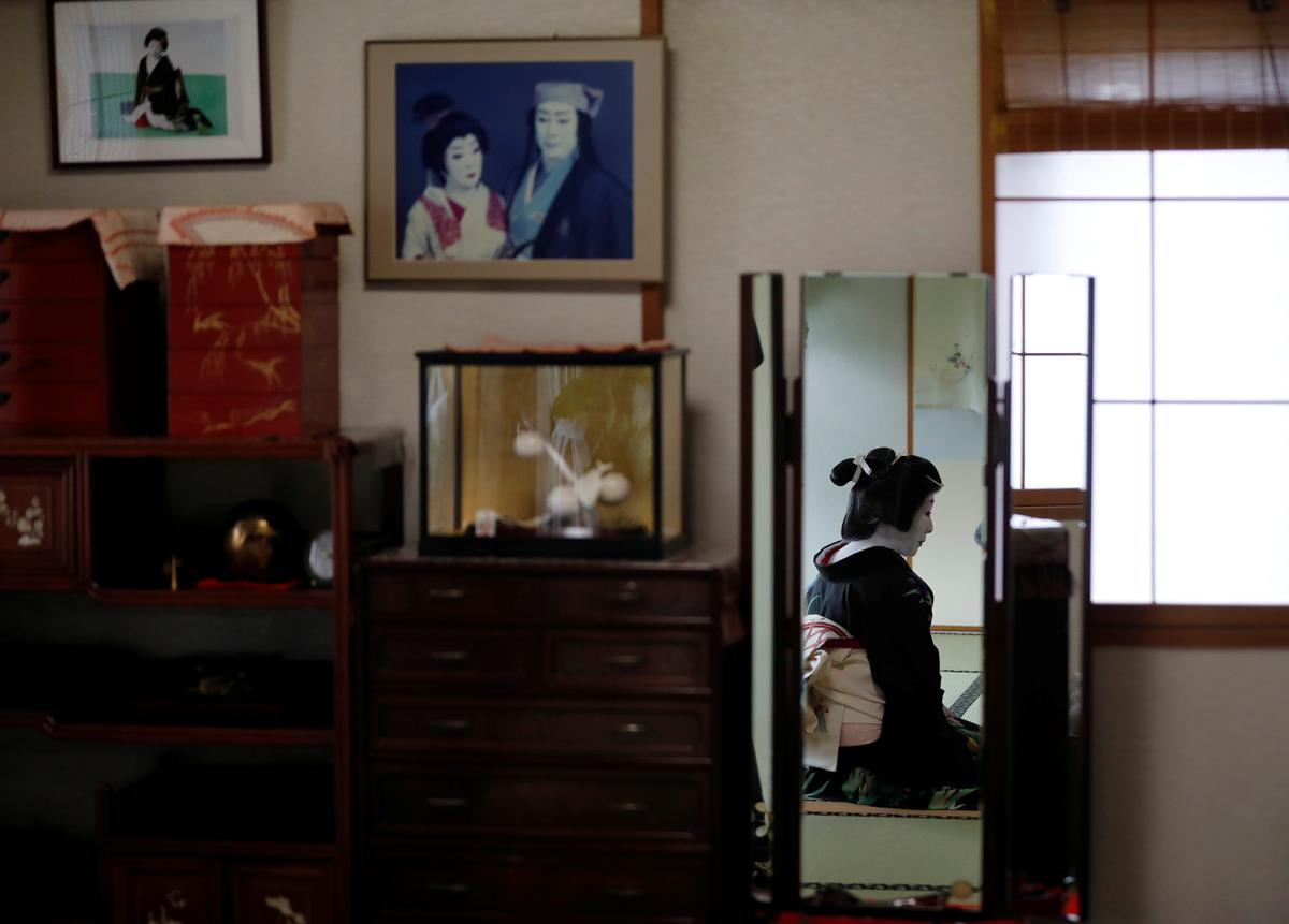 Ikuko, who is a geisha, sits in front of a mirror in her living room as she gets ready to work at a party being hosted by customers at a luxury restaurant, where she will be entertaining with other geisha, during the coronavirus (COVID-19) outbreak, in Tokyo, Japan, June 23, 2020. Photo: Reuters