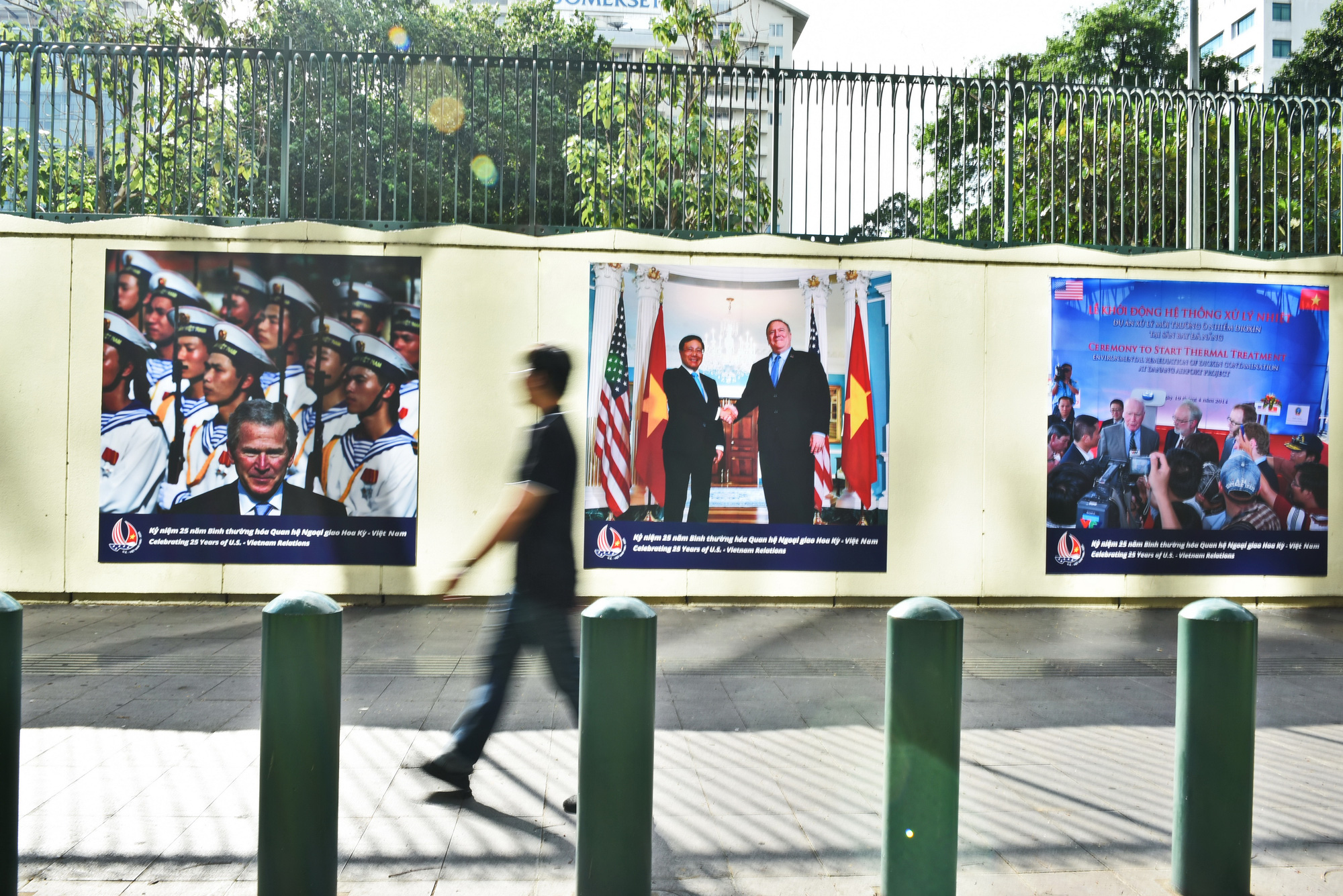 A man walks past photos displayed on the wall of the U.S. Consulate General in Ho Chi Minh City to mark the 25th anniversary of Vietnam-U.S. relations, July 16, 2020. Photo: Ngoc Phuong / Tuoi Tre