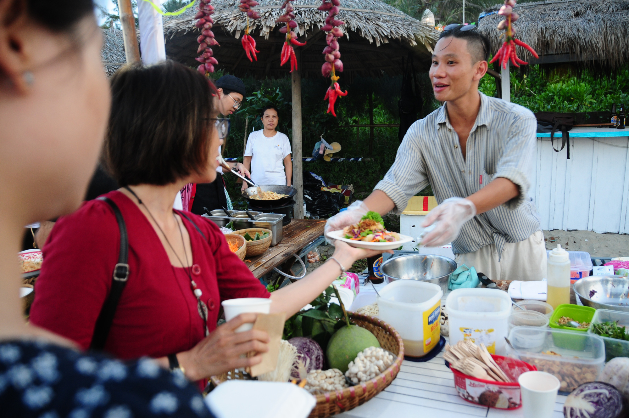 A woman receives food cooked by a chef at the 2020 An Bang Beach Food & Music Festival in Hoi An City, Quang Nam Province, Vietnam, July 18, 2020. Photo: B.D. / Tuoi Tre