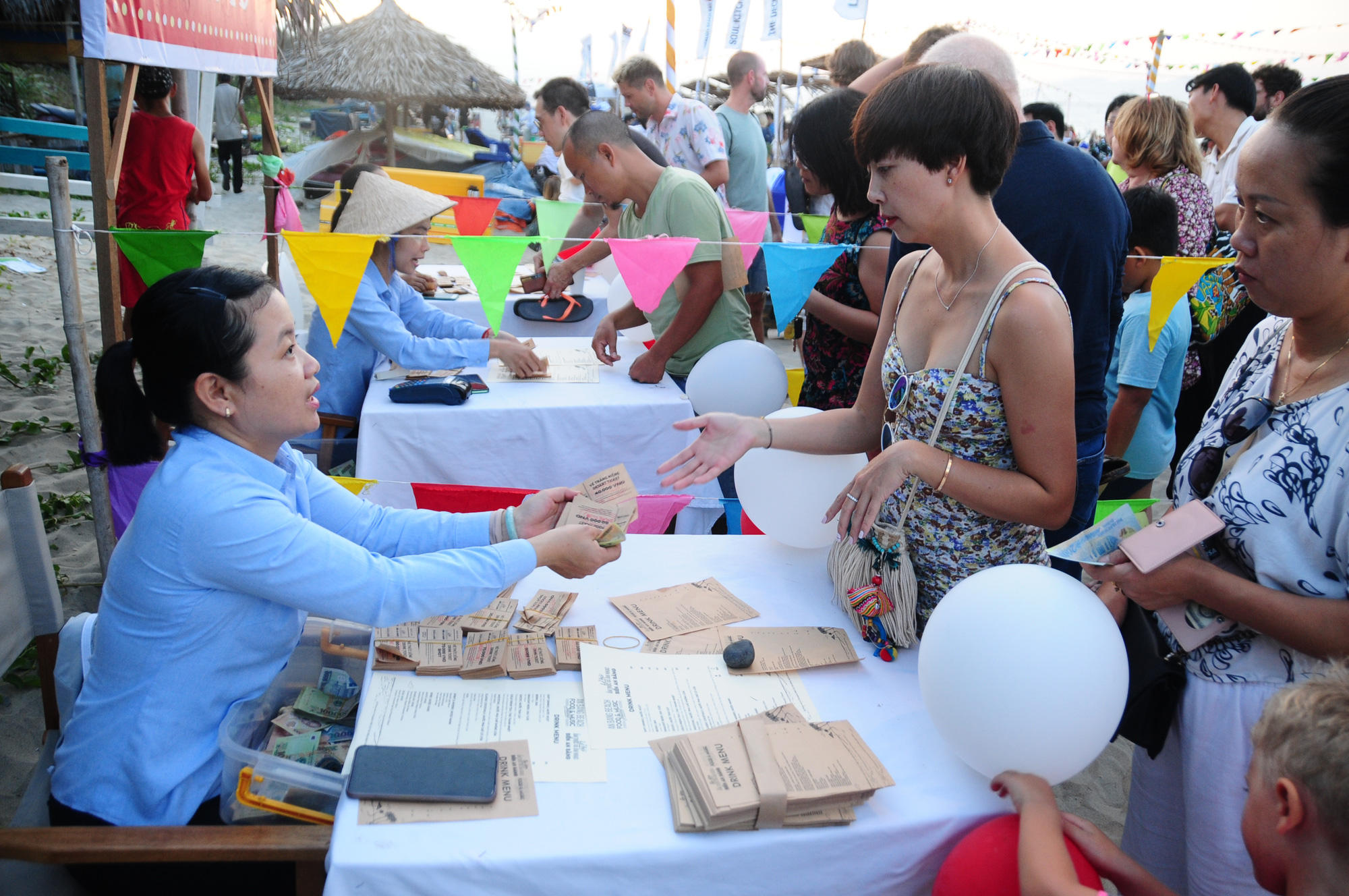 Visitors buy tickets to exchange for various dishes at the 2020 An Bang Beach Food & Music Festival in Hoi An City, Quang Nam Province, Vietnam, July 18, 2020. Photo: B.D. / Tuoi Tre